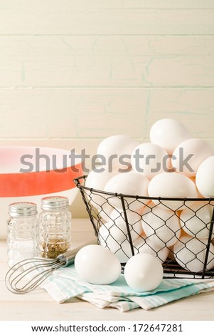 Fresh eggs rest in a wire basket with a vintage bowl and wire whisk, accented with old-fashioned salt and pepper shakers sitting ready for preparing breakfast. - stock photo