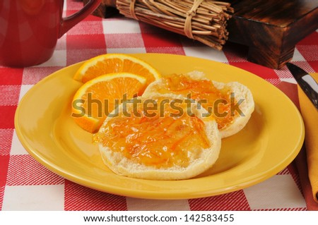 Fresh English muffins with orange marmalade - stock photo