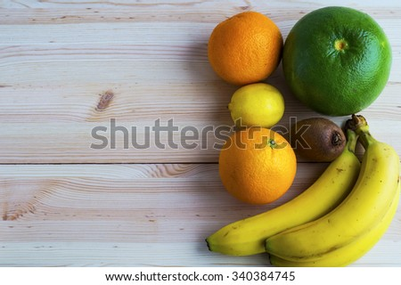 Fresh exotic fruits on wooden table background with copy space,  flat lay - stock photo