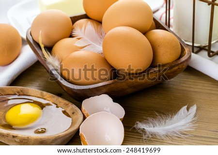 Fresh farm eggs, milk and butter on wood table.