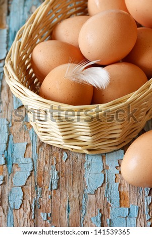 Fresh farm organic eggs with feather in a basket on an old wooden board.