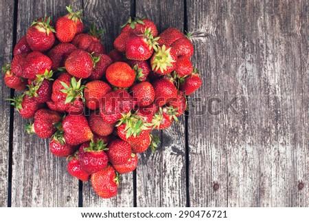 Fresh farmer strawberries on dark wood texture in shape of heart - stock photo