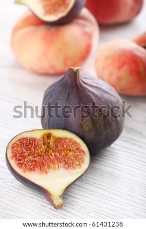 Fresh figs and peaches on the white wooden background