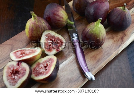 Fresh figs on wooden cutting board with knife on a dark wood vintage style table. - stock photo
