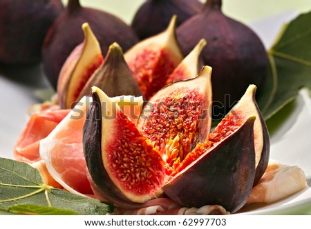 Fresh figs with ham on a white plate - stock photo