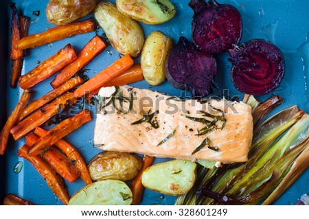 Fresh fillet of salmon with roasted vegetables served on a roasting tray. The vegetables include beetroot,carrots,potatoes and green beans. - stock photo