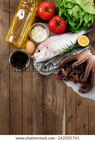 Fresh fish and vegetables on wooden table - stock photo