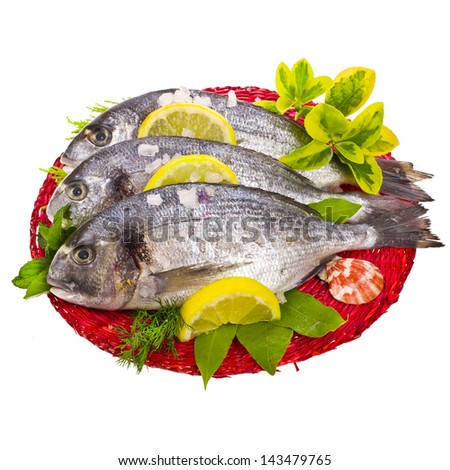 fresh fish bream,  with salt, lemon and decorated with leaves and herbs on the red circular woven mat isolated on white background - stock photo