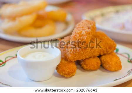 fresh fish fingers and white sauce on dish - stock photo