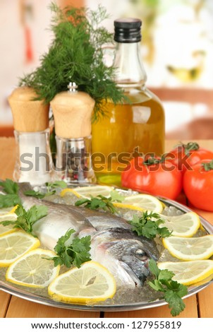 Fresh fish of dorado on tray with lemon and parsley on wooden table - stock photo