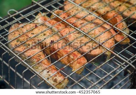 Fresh fish on grilling sticks. - stock photo