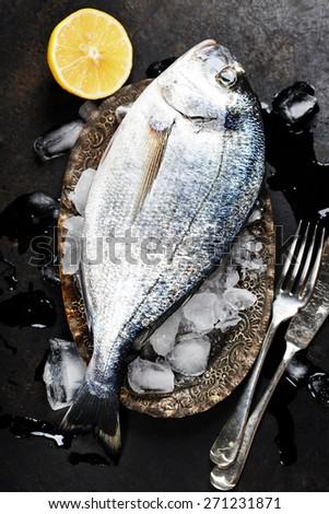 Fresh fish on ice (dark vintage background) - stock photo