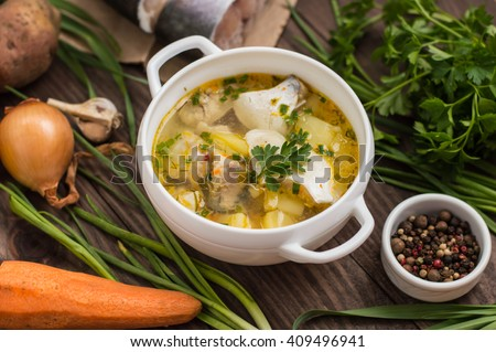Fresh fish soup with ingredients and spices for cooking. Wooden background  - stock photo