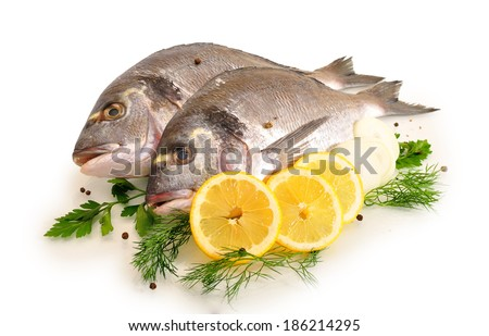 fresh fish with onion greens and lemon on white background - stock photo