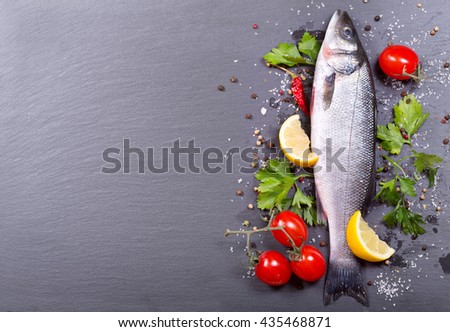 fresh fish with spices and vegetables on dark background - stock photo