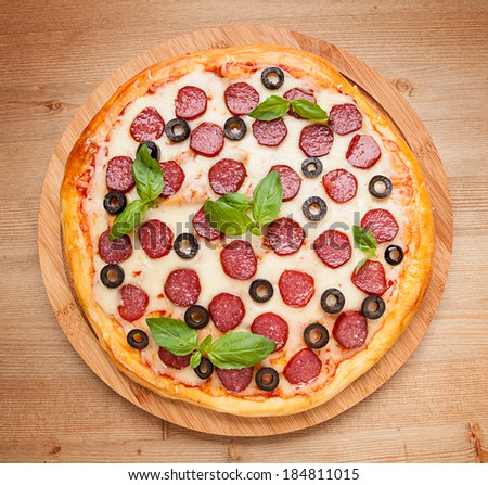 Fresh flavorful pepperoni pizza on wood  - stock photo