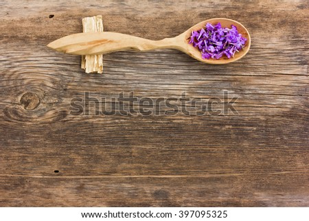 Fresh flower petals in a wooden spoon on the old board. aromatherapy, herbal tea, homeopathic medicine. Free space for text. Copy space - stock photo