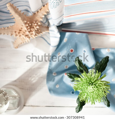 Fresh flower, starfish and a towel on wooden floor, overview shot, shallow focus on the flower. Summer holiday by sea and relaxation concept. Toned photo. - stock photo