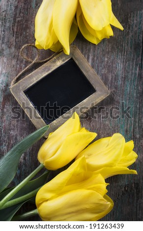 Fresh flowers and empty blackboard with place for text on aged wooden background. Top view. - stock photo