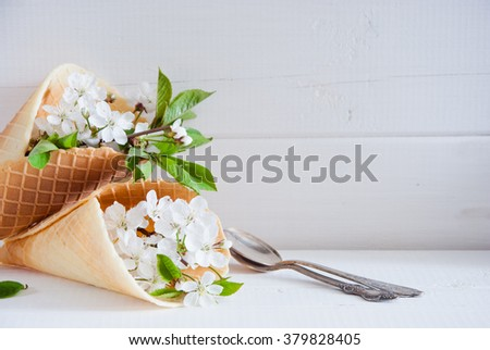 Fresh flowers in ice cream cone still life on a light wooden background
