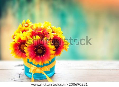 Fresh flowers in vase on wooden table. Vintage cyan background. - stock photo