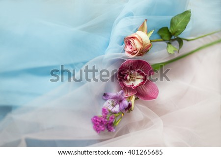 fresh flowers on the fabric blue pink tenderness - stock photo