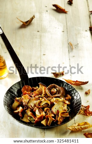 Fresh forest mushrooms from an autumn harvest sliced and prepared as a gourmet appetizer or healthy vegetarian meal in a frying pan on a white wooden table with copyspace - stock photo