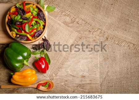 Fresh fragrant salad of colorful peppers with basil leaves and salad on the table - stock photo