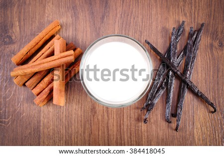 Fresh fragrant vanilla pods, cinnamon sticks and glass of milk on wooden surface plank, seasoning and ingredients for cooking or baking - stock photo