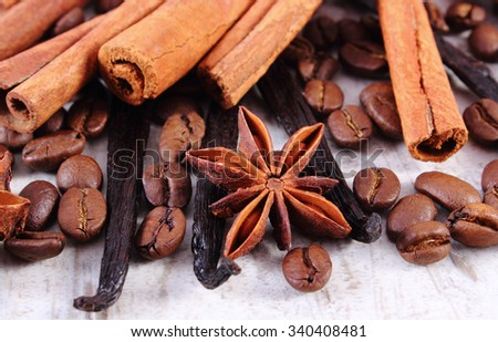 Fresh fragrant vanilla pods, cinnamon sticks, star anise and coffee grains on old rustic wooden surface plank, seasoning ingredients for cooking or baking - stock photo