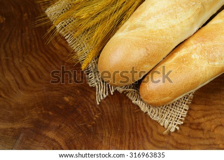 fresh French baguette (bread) on wooden background - stock photo