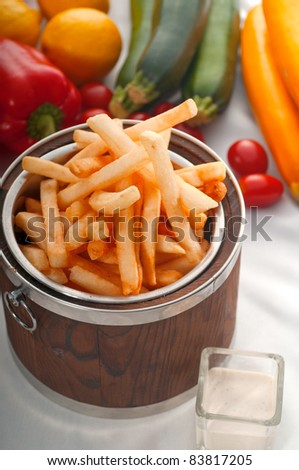 fresh french fries on a wood bucket with white dip sauce and fresh vegetables on background - stock photo