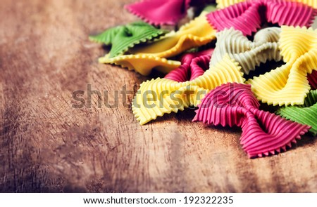 Fresh Fresh Italian Pasta on old vintage wooden background. Raw Bow tie colourful  pasta close up. - stock photo