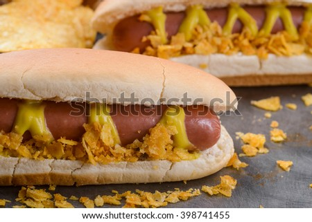 Fresh friable hotdogs with mustard and chips served on silver tray. Tasty sausages and soft bread for trully American fast food recipe.
