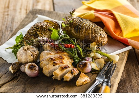 fresh fried chicken breast on wood plate with garlic, chili, potatos and some wild bailicum - stock photo