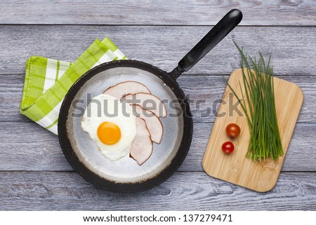 Fresh fried egg and pork ham served on pan with chives and tomatoes. English breakfast. - stock photo