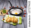 Fresh fried egg and pork ham served on pan with rolls, tomatoes and chives. English breakfast. - stock photo