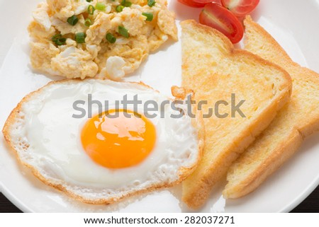 fresh fried egg and scrambled egg with bread for breakfast - stock photo