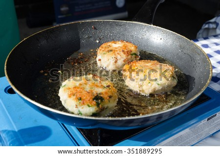 Fresh fried fish cakes  pan frying in the sunlight - stock photo