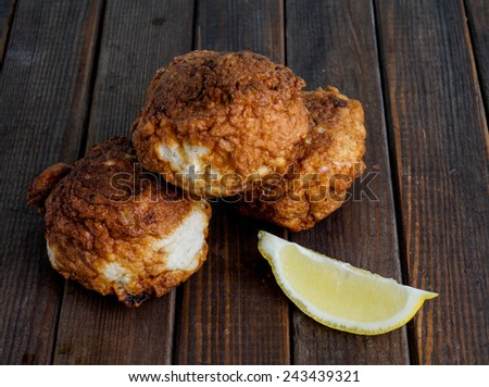 Fresh fried fish cakes served with lemon - stock photo