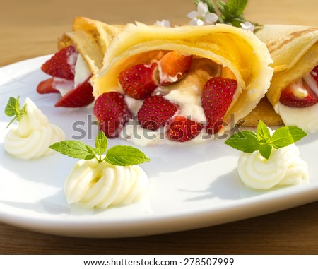 Fresh fried golden pancake filled with strawberries, whipped cream and garnished with mint
