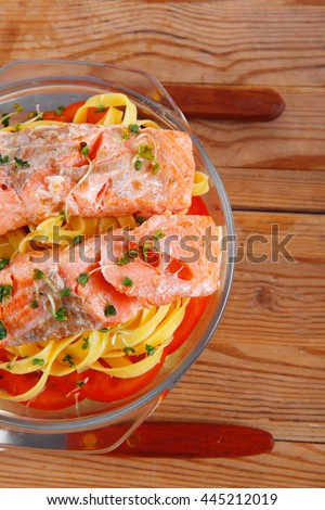 fresh fried natural pink salmon on italian traditional tagliatelle backed with tomato and vegetables served over wooden table with cutlery - stock photo