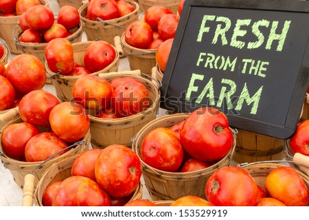 Fresh from the Farm chalk board sign display with baskets full of locally grown red tomatoes at local farmers market - stock photo