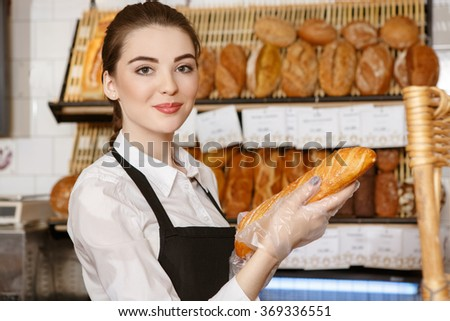 Fresh from the oven. Gorgeous baker woman holding freshly baked bread smiling to the camera happily  - stock photo