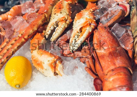 fresh frozen lobster on ice with lemon at market - stock photo