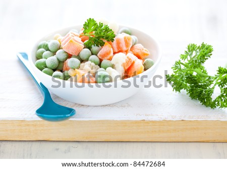 fresh frozen mixed vegetables in bowl with parsley - stock photo