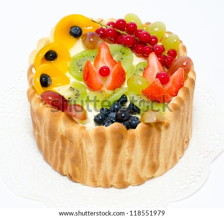 fresh fruit and berries on whipped cream in a sponge basket - stock photo