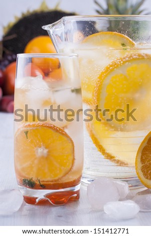 Fresh fruit and water drink with a orange slices, mint herb and ice cubes with some fruits in the background.