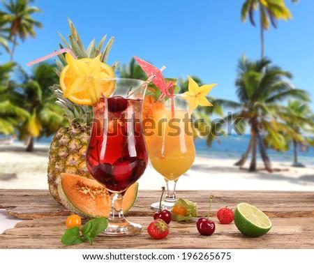 Fresh fruit drinks on sandy beach - stock photo