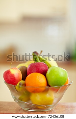 Fresh fruit in a bowl standing in a kitchen